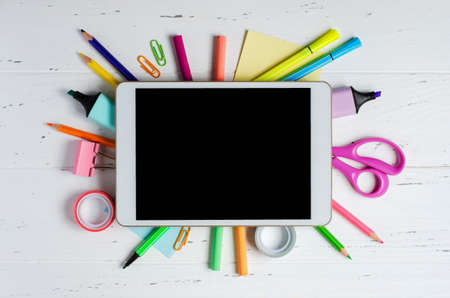 A tablet with an empty screen and office supplies on a white wooden background. Concept app for school children or online learning for children. Copy space.