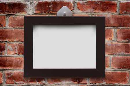 A wooden frame hangs on the brown brick wall. Copy space