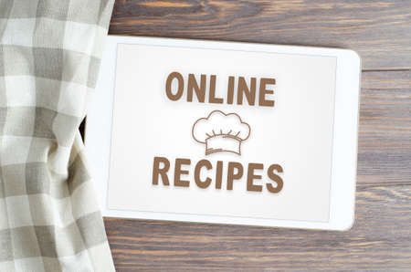 Online recipes. App in smartphone. Brown wooden background. Фото со стока