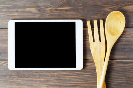 A tablet computer and wooden spoon and fork on a brown background. Copy space. Concept of cooking recipes Фото со стока