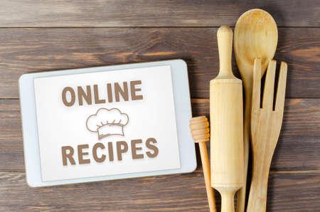 Online recipes. Cookbook in a tablet computer. Kitchen utensils. Brown wooden background