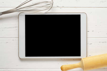 A tablet computer and cooking battery on a white background. Copy space. Concept of cooking recipes