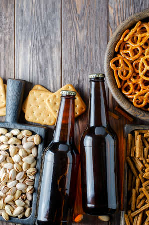 Beer in glass bottles and salty snacks for beer in wooden dishes. Rustic style. Brown wooden background. Copy space