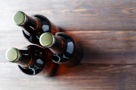 Three glass bottles of dark beer stand on a brown wooden background. The view from the top. Copy space
