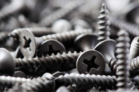 Lots of metal screws in close-up. Background of fixing tools. Macrophotography