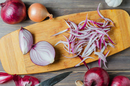Red onion sliced. The process of cooking on a yellow cutting Board. Flat top view