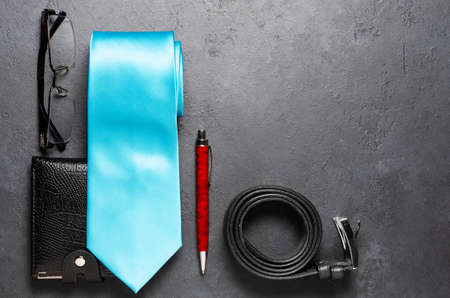 Mens accessories on a black concrete background. The concept of a successful modern man. Copy space