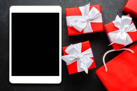 Red gift boxes and a tablet with a blank screen for text. Copy space