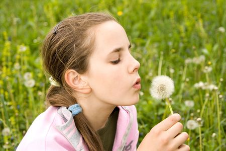 careless: Young girl blowing seeds of a dandelion on meadow grass and fun.
