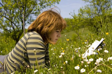careless: Young woman read a book on meadow field .