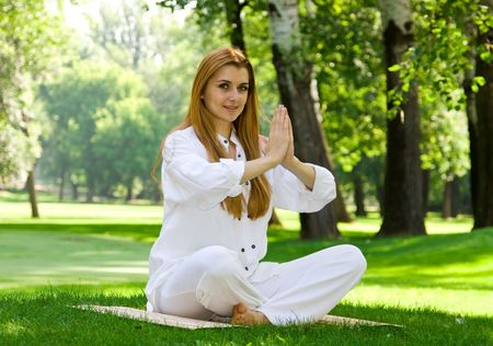 Beautiful woman in white doing yoga outdoors. Stock Photo