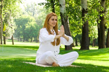Beautiful woman in white doing yoga outdoors. Stock Photo - 3148051
