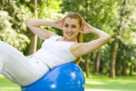Fitness girl outdoor exercise by pilates ball. Stock Photo