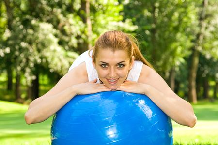 Fitness girl outdoor exercise by pilates ball. photo