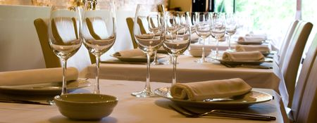 restaurant setting: Glasses of wine set at restaurant table.