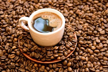 Cup with coffee over roasted coffee-bean.