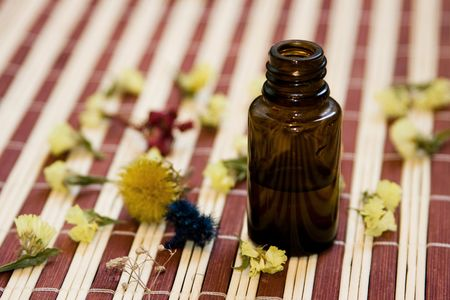 prying: Essential oil and dried flower on bamboo background. Stock Photo