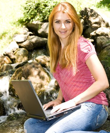 Beautiful young student using laptop in natural environment. photo