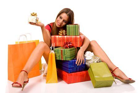 euforia: Atractivo ni�a sentada en el suelo y buscando caja de regalo con muchas cajas y bolsas alrededor. Foto de archivo