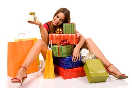 Attractive girl sitting on floor and looking gift box with many boxes and bags around. Stock Photo - 3720672