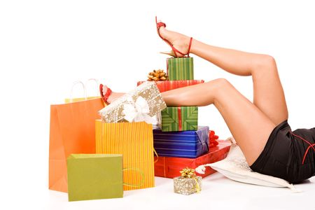 Attractive woman legs over many gift boxes and bags. photo