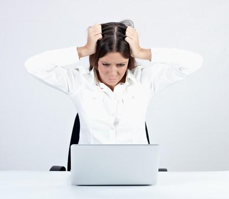 nip: Frustrated businesswoman using laptop.