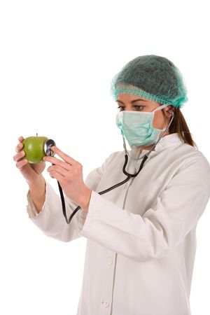 ordination: Doctor checking green apple by stethoscope isolated on white.