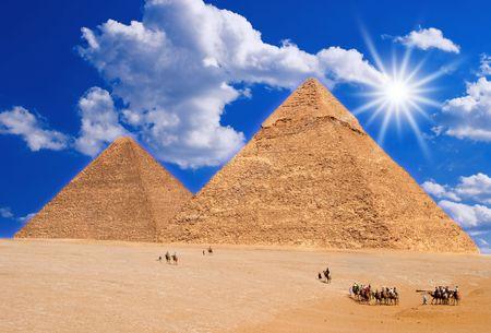 desert sun: Camel caravan going to pyramids on hot desert sun.