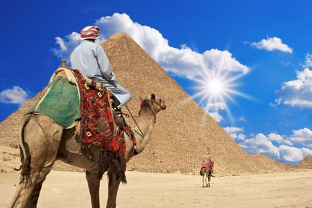 Bedouin ride camel against pyramid on hot desert sun. Stock Photo - 4803083