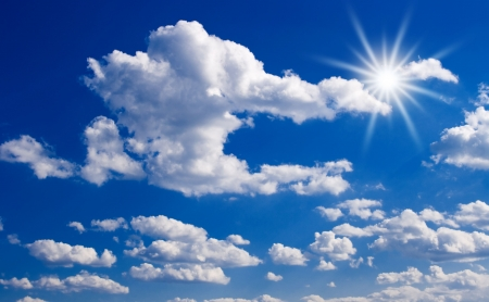 Blue sky with clouds and sun rays.