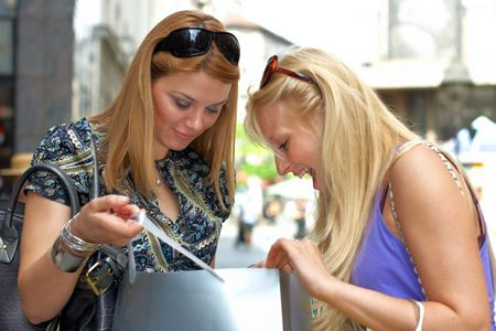 Excited shopping woman looking what her friend purchase in street environment. Stock Photo - 4891923