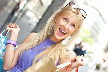 Excited shopping woman with bags in city environment. Stock Photo - 4891922