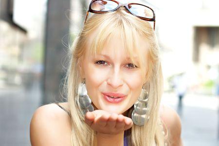 Beautiful woman sending kiss over city enviroment. Stock Photo - 4891921