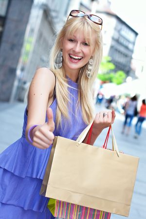 approved sign: Beautiful shopping woman with bags show approved sign by hand in the city. Stock Photo
