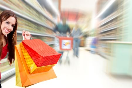 Shopping woman holding bag over blurred supermarket background.