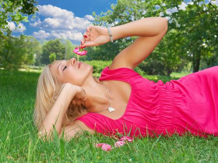 Beautiful woman relax on grass and smell flower. Stock Photo - 5233849
