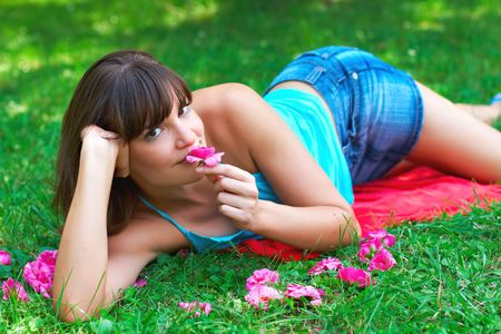 Attractive woman relax on grass and smell flower. Stock Photo - 5233850