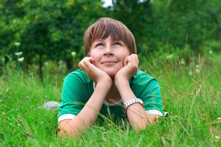 Boy laying down on grass and looking above. photo