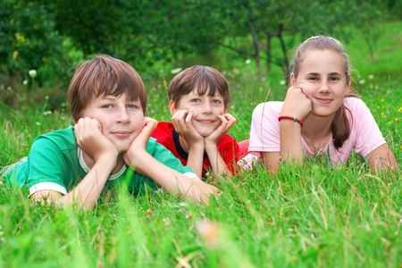 Three happiness children laying on the grass. Stock Photo - 5283227