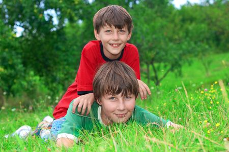 Brothers fun outdoor on grass. photo