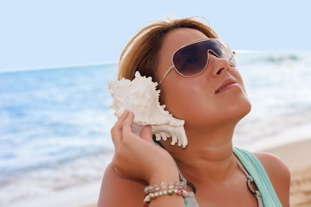 Beautiful woman listening counch shell sound on the beach. photo