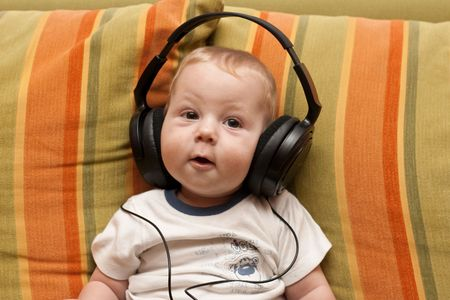 Baby listening music by headphones. photo