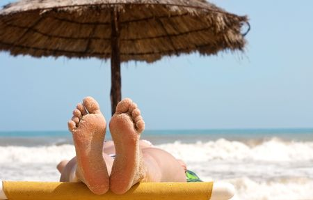 feet relaxing: Woman feet with sand on the beach and sea in the background. Stock Photo