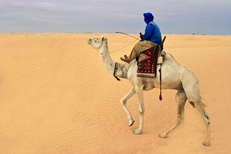 Bedouin riding camel in desert Sahara. photo