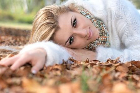 Beautiful young woman relaxing on leaves in the park. Stock Photo - 5996258