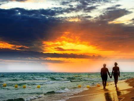 along: Lovers walk along the beach at sunset. Stock Photo