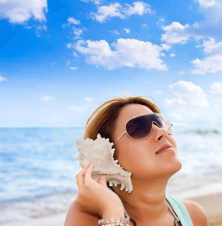 Beautiful woman listening counch shell sound on the beach. Stock Photo - 8111984