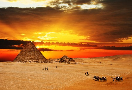 Camel caravan going through desert in front of pyramid at sunset.