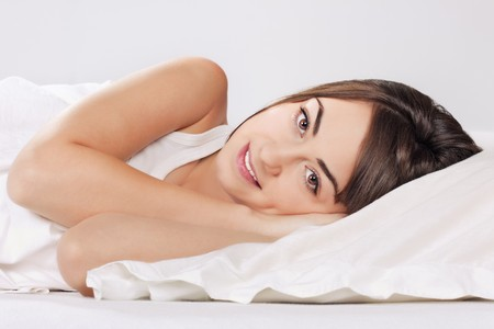 Portrait of beautiful young woman relaxing on the bed. Stock Photo - 8179589