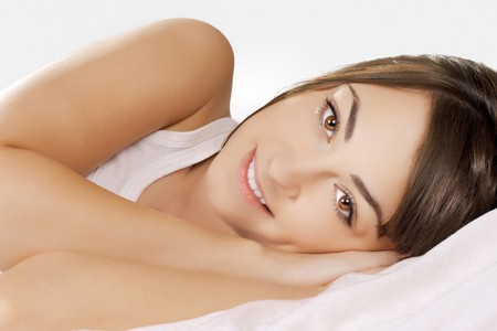 Portrait of beautiful young woman relaxing on the bed. photo